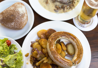 Traditional German meal with sausage, potato and beer