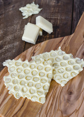 White chocolate on rustic wooden background.