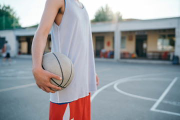 Cropped view of man on basketball court holding basketball