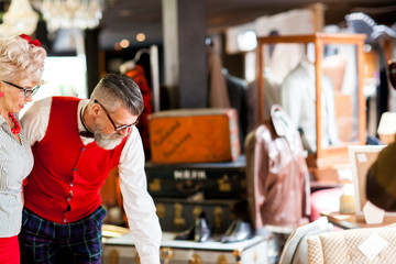Quirky vintage couple looking down in antiques and vintage emporium