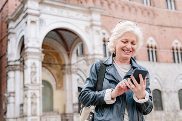 Mature woman looking at smartphone in city, Siena, Tuscany, Italy