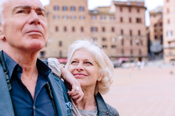 Mature woman gazing at husband in town square, Siena, Tuscany, Italy