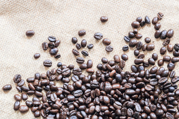 dark brown coffee beans on a brown bag.