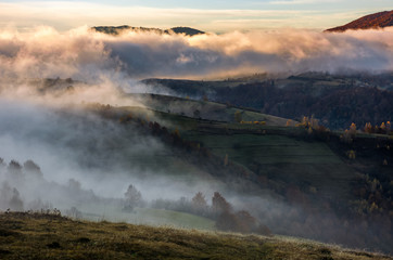 thick fog on hills in countryside at sunrise