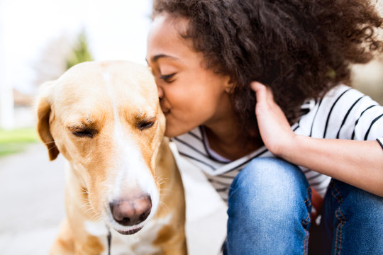 African american girl outdoors with her dog, kissing him.