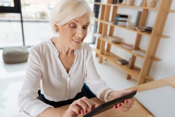 Joyful smart woman holding a tablet