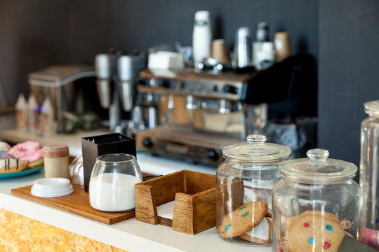Bar counter with biscuits, donuts and sugar in the coffee house, against the background of the coffee machine