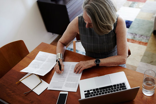 Senior businesswoman sitting at desk, laptop in front of her, signing document