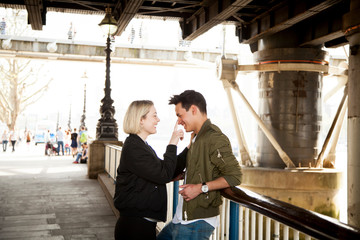 Young couple, standing underneath bridge, young woman touching man's face, smiling