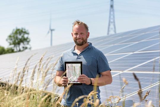 Local community member using digital tablet app to look at energy performance of solar farm