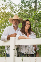 Mature couple leaning against ranch fence gazing, Bridger, Montana, USA