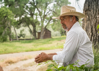 Mature man in cowboy hat leaning against ranch fence, Bridger, Montana, USA
