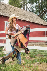 Young woman on farm, holding saddle