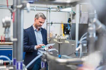 Businessman in factory using digital tablet