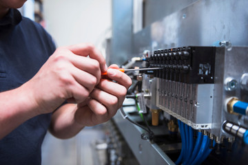Man using screwdriver on circuit board