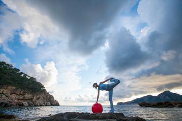 Woman with medicine ball standing on rocks, Palma de Mallorca, Islas Baleares, Spain, Europe