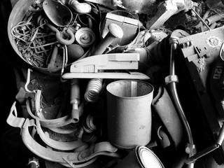 Stillleben mit Hefter, Kaffeebecher und altem Metall in einer alten Scheune in Rottenbuch in Oberbayern, fotografiert in neorealistischem Schwarzweiß