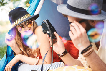 Young boho couple lying in tent looking at camera at festival