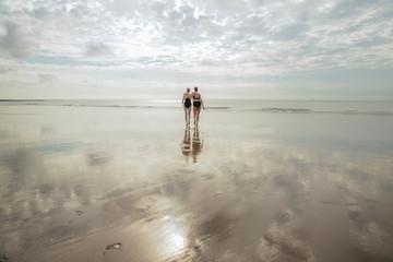 Women in swimwear embracing and walking on beach