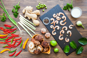 Ingredients for famous thailand spicy hot soup with red chilly peppers, shrimp, lemongrass leaf, shiitake mushrooms, ginger root, coconut milk, garlic and lime. Tom Yum Kung. Asian Dish Cuisine. Top.