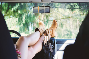 Young woman in ankle boots with feet up in recreational van