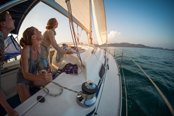 Three young women adjust the genoa sail after entering in a calm area of a tropical sea