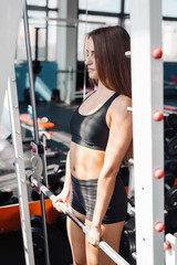 Woman doing shoulder press exercise with weight bar in gym
