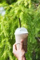 Woman hand is holding an cold coffee cup.