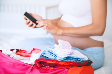 Pregnant woman packing for hospital and taking notes in smart phone