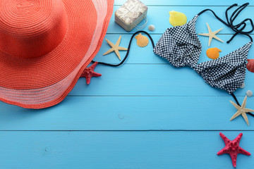 Summer time of the year, vacation, weekend, vacation, travel. Marine background (frame) of a swimsuit, cap, starfish and seashells on a blue wooden background.