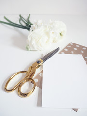 Styled stock photo. Feminine digital product mockup with buttercup and daffodil flowers, blank list of paper and golden scissors. White background. Flat lay, top view.