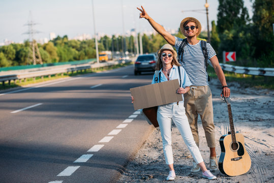 young couple in love with empty cardboard hitchhiking while traveling together