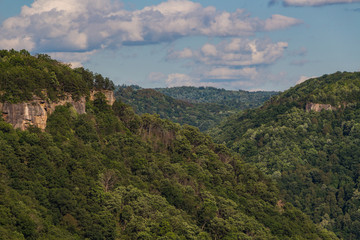 Southern West Virginia mountain tops with rock outcrops visible through the green trees of summertime and a cloudy blue sky overhead.