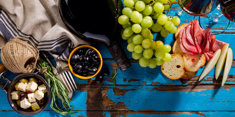 Tasty appetizing italian Mediterranean Greek Food Ingredients Wine Grape Meat Olives Cheese on Blue Old Table