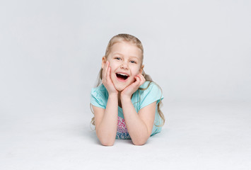 Happy little girl lying on the floor on white studio background