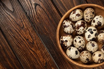 top view on quail eggs in wooden plate over old wooden background