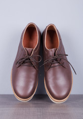 Brown leather men's shoes on a wood and wall background
