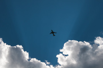 the silhouette of the plane against the sky and clouds,