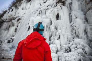 Rear view of climber in red jacket looking at hill in ice