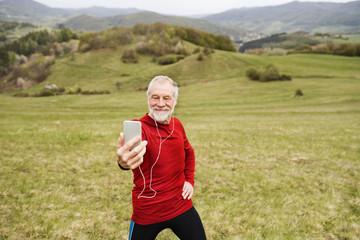 Active senior runner in nature taking selfie with smart phone.