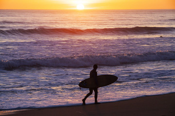 Man holding surfing board walking on beach at sunset