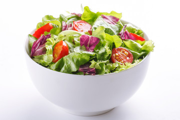 Fresh salad in a bowl. Healthy lettuce and tomato meal on white background