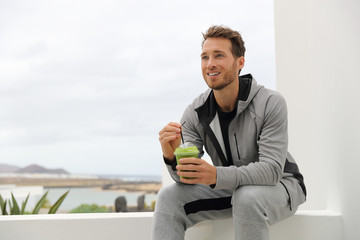 Healthy man drinking green smoothie at home terrace. Sport athlete with spinach cold pressed juice plastic cup drink relaxing outdoors.