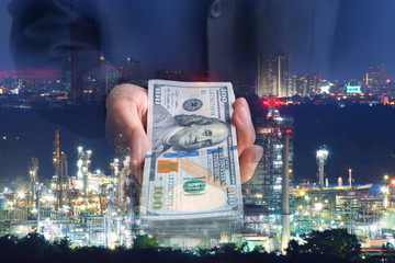 Multiple exposures of Invester offers US dollars money with oil refinery background as in business concept.