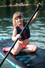 Little girl on sup board paddling on lake