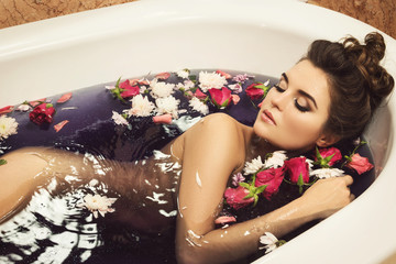 Beautiful woman in the bath with flowers