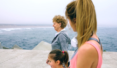 Three female generations walking by sea pier. Selective focus on senior woman in background