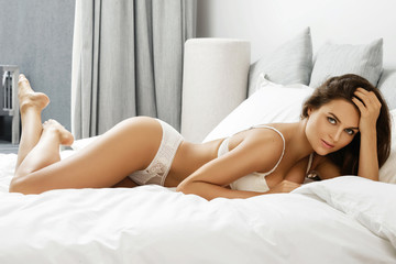 Sexy woman in white lingerie in the bed