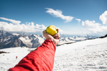 A man's hand holds an apple with a bite on the background of snow-covered mountains and snow underfoot.