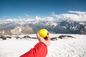 A man's hand holds an apple against the background of snow-capped mountains and snow underfoot.